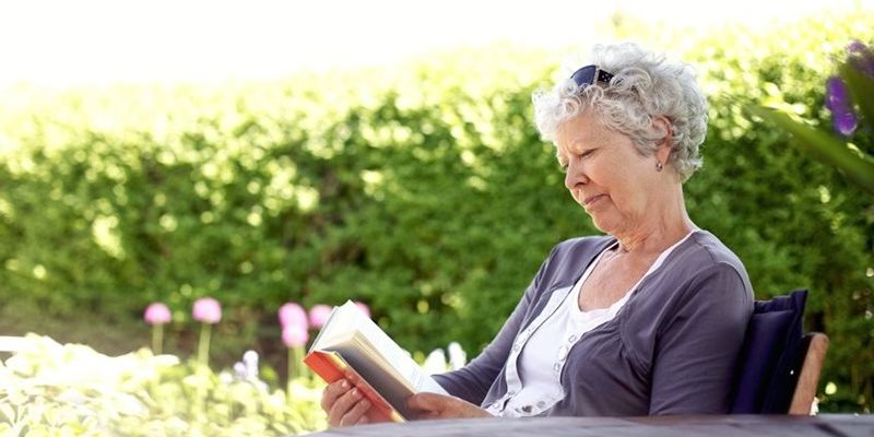 Woman reading a book in garden